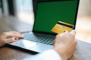 mulher com um laptop e um cartão de crédito