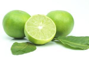 limão verde com folhas isoladas no fundo branco
