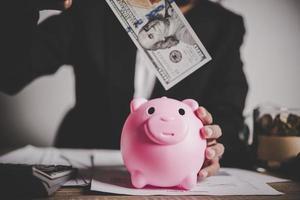 mulher colocando nota de euro em um cofrinho foto