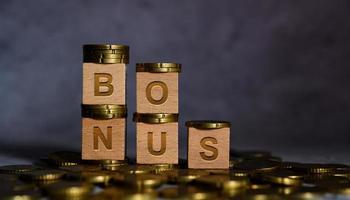 palavra bônus em letras de cubo de madeira colocadas em uma moeda de ouro foto