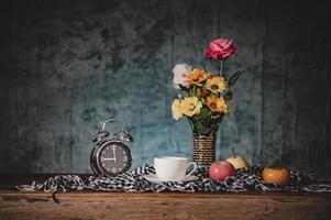 natureza morta com vasos, flores, frutas, xícaras de café e relógios foto