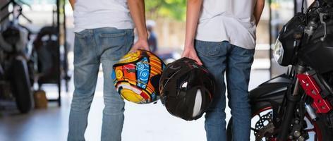 casal de viajantes carregando capacetes de motocicleta