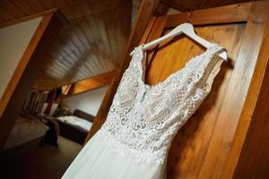 vestido de noiva nos ombros no armário
