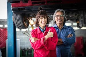 técnica feminina de retrato e seu supervisor na frente de um carro em uma garagem