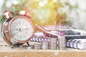moedas empilhadas com despertador foto