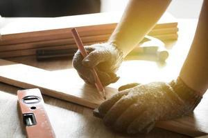 carpinteiro medindo e escrevendo na madeira foto
