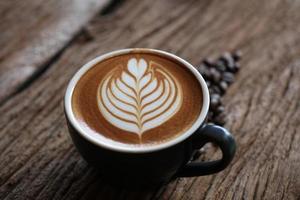 Café cappuccino quente com arte em formato de folha em mesa de madeira foto