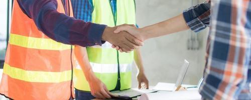 dois trabalhadores da construção civil apertando as mãos foto