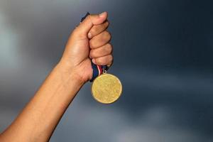 pessoa segurando uma medalha de ouro