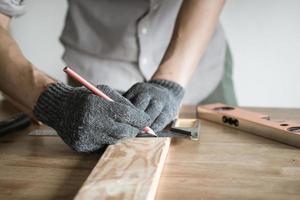 carpinteiro medindo madeira com lápis foto