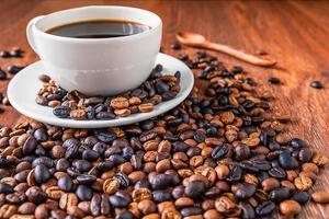 xícara de café e grãos de café em uma mesa de madeira