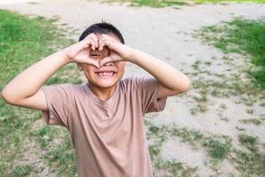 menino fazendo um coração com as mãos