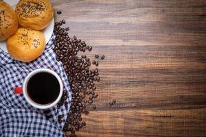 grãos de café com pão fresco foto
