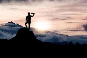 silhueta de pessoa em pé na montanha com um troféu foto