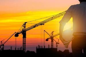 pessoa segurando capacete olhando para guindastes de construção ao pôr do sol foto