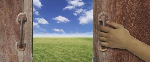 mão abrindo uma porta de madeira para um lindo ambiente externo foto