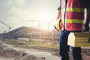 trabalhador da construção civil segurando a caixa de ferramentas e o capacete foto