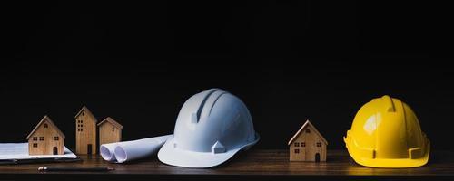 dois capacetes e casas modelo em fundo preto foto
