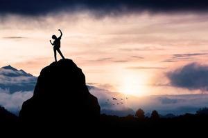 pessoa em cima de uma rocha ao pôr do sol foto