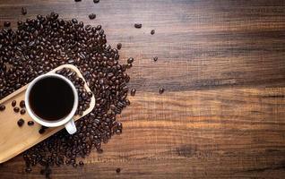 grãos de café com xícara na mesa de madeira