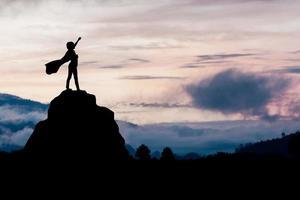pessoa com capa de pé em uma grande rocha foto