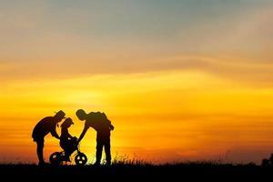 silhueta de pais ajudando filha a andar de bicicleta foto