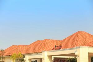 telhas laranja no telhado de uma casa contra um fundo de céu azul foto