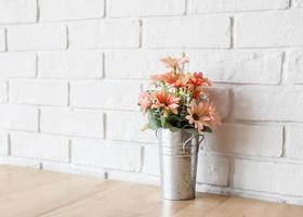 uma parede branca e uma flor decorativa em uma mesa de madeira foto