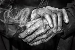 velhas mãos segurando um cachimbo com fumaça