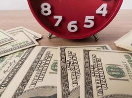 notas de dólar na mesa e despertador vermelho foto