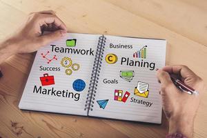 close-up de mãos escrevendo no papel com o ícone de doodle colorido de negócios