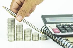 caneta, moedas e calculadora em fundo branco