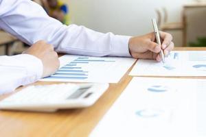 empresário escrevendo em tabelas e gráficos