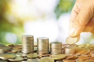 mão empilhando moedas foto