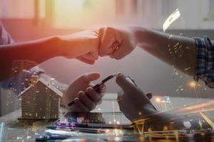 duas pessoas batendo os punhos com a sobreposição de paisagem urbana foto