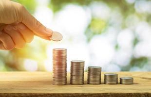 mão empilhando moedas de dinheiro em piso de madeira foto