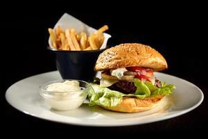 hambúrguer com batatas fritas no prato foto