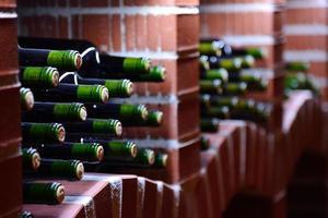 garrafas de vinho em repouso empilhadas em um cofre de tijolos de pedra foto