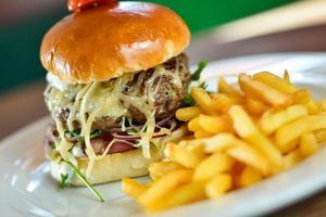 hambúrguer com batata frita no prato foto