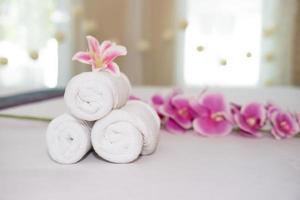 linda orquídea rosa em toalha branca em salão de spa foto