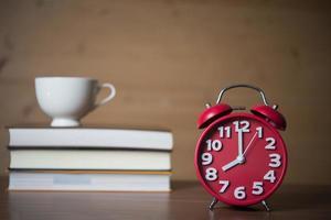 despertador às 8h e pilha de livros com café