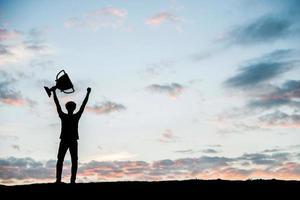 homem silhueta segurando uma taça de troféu foto