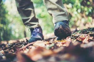 close-up dos pés de um alpinista caminhando em uma trilha na montanha
