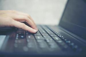mão de mulher digitando com laptop foto