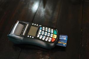 máquina de cartão de crédito com cartão de crédito inserido na mesa de madeira foto