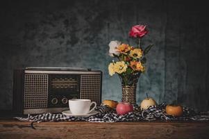 natureza morta com vasos, flores, frutas, xícaras de café e um receptor de rádio retrô
