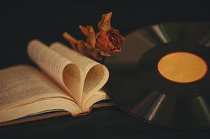 natureza morta com livros em formato de coração, flores secas e CD antigo foto