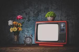natureza morta retro da tv com relógios e vasos de flores foto