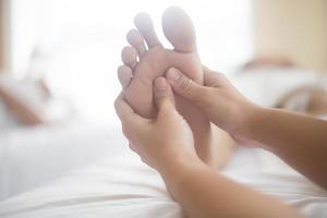 mulher fazendo massagem nos pés em um salão de beleza