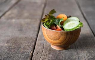 salada de legumes fresca em fundo de madeira foto